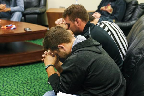 UND student athletes from the suspended baseball program (from left) Zach Heaser and Daniel Lockhert pray during a Fellowship of Christian Athletes (FCA) meeting Monday evening at the Betty Engelstad Sioux Center. FCA is represented by roughly thirteen athletic teams on campus, with the majority coming from women's basketball and softball.