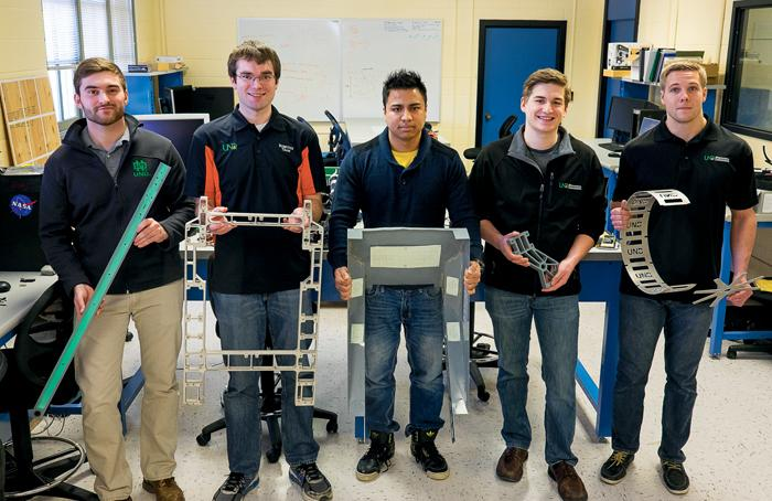 Members of the UND Robotics team stand holding components of their most recent robotic vehicle.