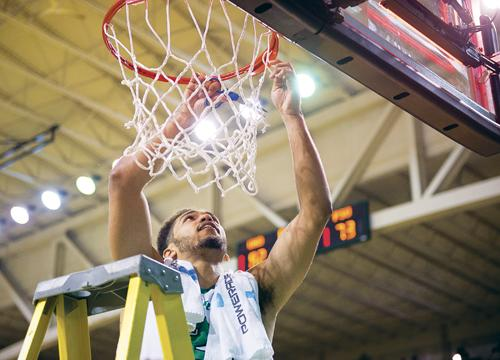 Senior guard Quinton Hooker cuts a piece of the net in celebration following Saturday's win against Portland State and UND's Big Sky regular season championship. Nick Nelson/ Dakota Student