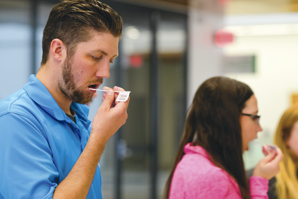 Paul Samson (left), medical lab science education specialist, and Shanalee Mountain (right), medical student, swab their mouths during a bone marrow volunteer drive on Wednesday, April 26, 2017 at the Medical School.