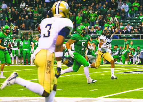 Brady Oliveira runs the ball against Montana State University during the Hall of Fame game at the Alerus Center last season.  Photo by Nick Nelson/ The Dakota Student