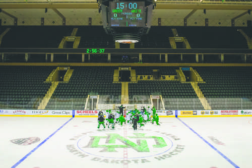 The UND men's hockey team gathers around head coach Brad Berry during practice at the Ralph Engelstad Arena on Friday, September 23, 2016.