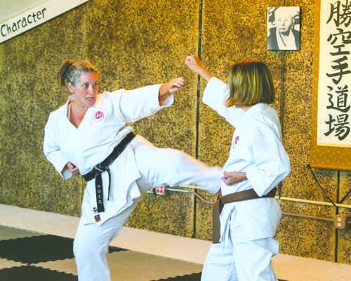 LaRoyce Batchelor demonstrates a kick with Karen Katrinak at the Hisshou Karate Dojo in Grand Forks, N.D. on Saturday, September 3, 2016. Photo by Daniel Yun/ The Dakota Student