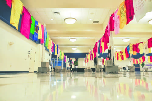 UND students walk among rows of t-shirts during the Clothesline Project in the Memorial Union ballroom on Tuesday, October 4, 2016.