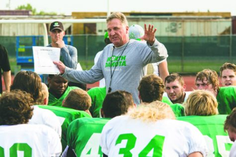 Head coach Bubba Schweigert addresses the football team after practice at Memorial Stadium in 2015.