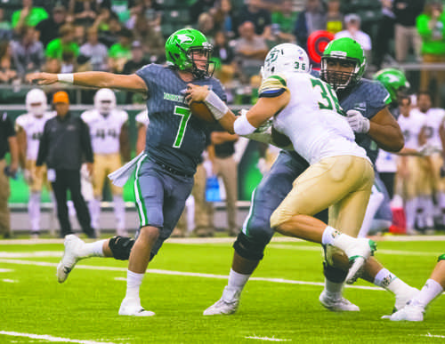 UND quarterback Keaton Studsrud (left) runs the ball against Cal Poly State linebacker Joseph Gigantino during Saturday's game at the Alerus Center.