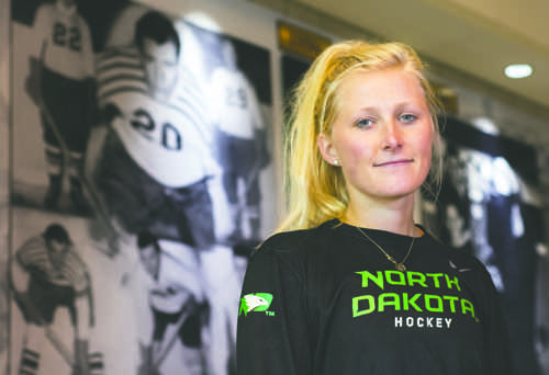 Lisa Marvin, a junior forward on the UND women's hockey team, stands in front of a mural dispaying her grandfather, Calvin Coolidge Marvin, who co-founded the men's hockey team.