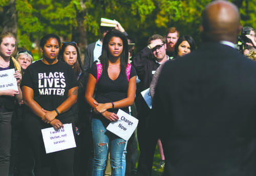 Selena Kibira (BLM shirt) and her friend Sade Lawal listen as Roy Roach speaks during the Zero-Tolerance rally outside Twamley Hall on Friday, September 30, 2016.
