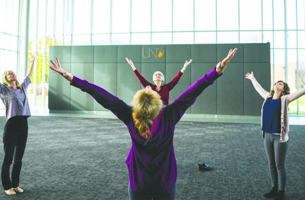 Kay Williams (front center) leads Ashley Watermolen (left), Marsy Schroeder (rear center) and Jessie Hoeger (right) in stretching during a Zen in 10 event at the Gorecki Alumni Center on Tuesday morning.