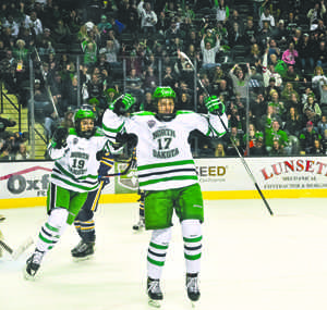 Tyson Jost (right) and Shane Gersich (left) celebrate Jost's first UND career goal Friday evening against Canisius University at the Ralph Engelstad Arena.
