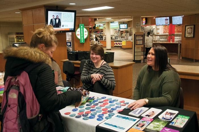 Samantha Hinnenkamp (left) and Jenna Desmidt (right) speak to a student at the Love Your Body table Monday afternoon in the Memorial Union.