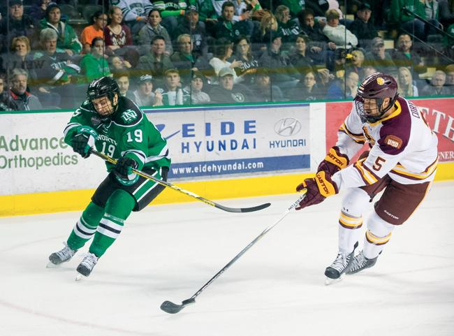 UND sophomore Shane Gersich fights for puck possession with Minnesota Duluth's Nick Wolff last season at the Ralph Engelstad Arena.