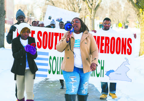 Elizabeth Nfor (center) leads students in a solidarity march on campus for Cameroon on Friday afternoon. Nick Nelson / Dakota Studenr