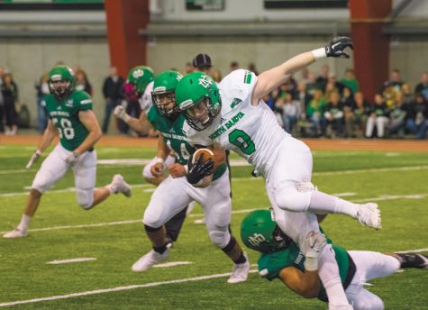 Cole Reyes (center) runs the ball during a green and white scrimmage last spring at the High Performance Center.