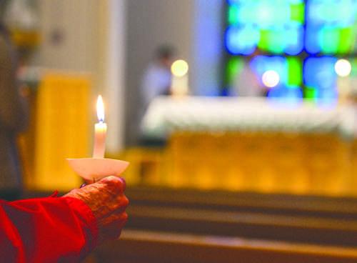 A parishoner holds a candle during Candlemass at the Newman Center, an Interfaith campus event, on Thursday evening. Daniel Yun/ Dakota Student