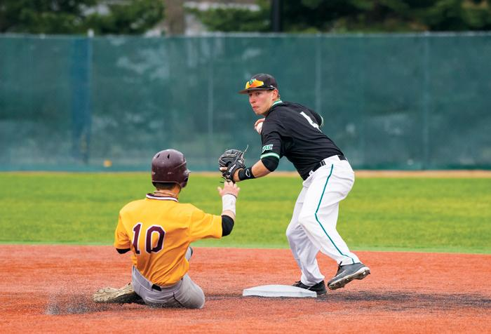 Former UND baseball player Ben Reznicek (right) tags out a University of Minnesota Crookston runner in the team's last season before the program was eliminated.