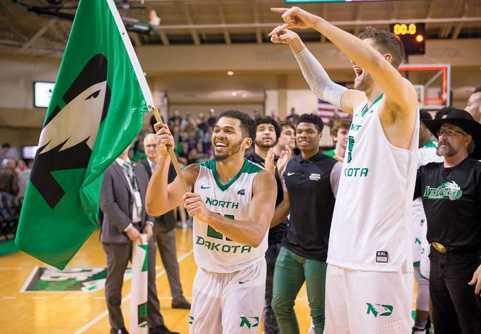 Quinton Hooker carries a flag bearing the UND Fighting Hawks logo around the Betty Engelstad Arena following the regular season Big Sky championship win over Portland State last Saturday.