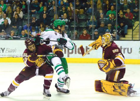 UND junior forward Austin Poganski is blocked by Minnesota Duluth