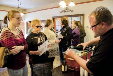 Guests sample wine at Mamma Maria's during Saurday's Art & Wine Walk.