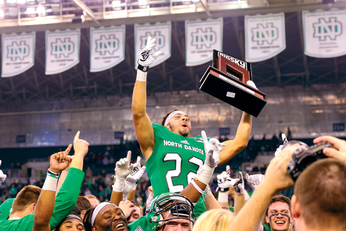 UND running back John Santiago hoists the 2016 Big Sky Conference football championship trophy after defeating Northern Arizona University at the Alerus Center on November 12, 2016.