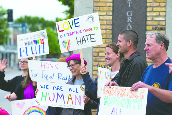 Rally goers wave hand-painted signs during an equality rally on Saturday in East Grand Forks, M.N. Nick Nelson/Dakota Student
