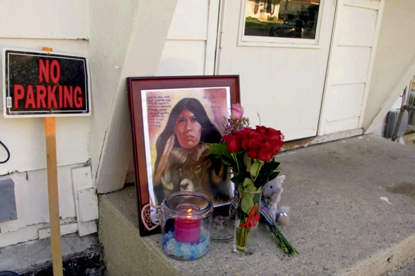 A makeshift memorial to Savanna LaFontaine-Greywind outside the apartment where she lived with her parents in Fargo, N.D. has flowers, a painting, candle and stuffed animal on Aug. 28, 2017. (Dave Kolpack/Associated Press)
