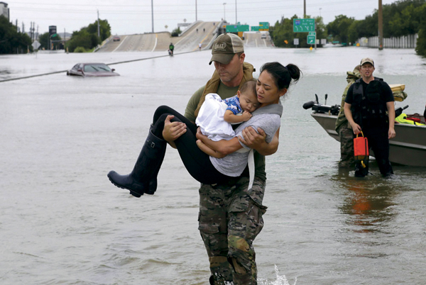 Houston Police SWAT officer Daryl Hudeck carries Catherine Pham and her 13-month-old son Aiden after rescuing them from their home surrounded by floodwaters from Tropical Storm Harvey Sunday, Aug. 27, 2017, in Houston. The remnants of Hurricane Harvey sent devastating floods pouring into Houston Sunday as rising water chased thousands of people to rooftops or higher ground.
