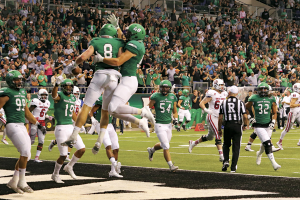 Cole Reyes (center left) and Jake Disterhaupt (center right) celebrate a touchdown by jumping for joy against South Dakota at last season's Potato Bowl game.