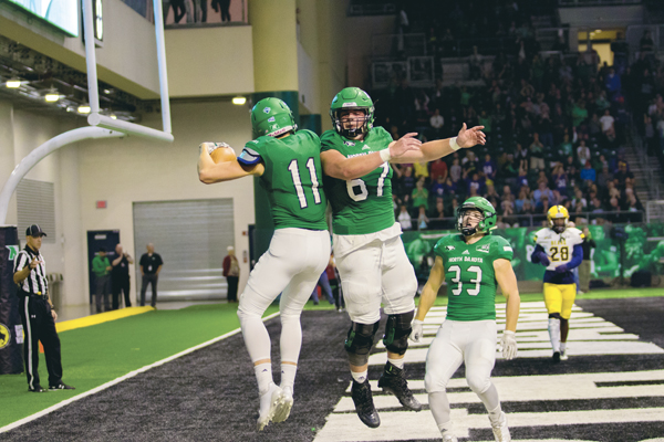 UND's Patric Rooney (center) and James Johannesson (right) celebrate Travis Toivonen's (left) first quarter touchdown against Northern Colorado Saturday at the Alerus Center.