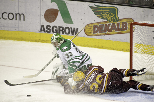 UND goalie Cam Johnson reaches for the puck as Minnesota's Darian Romanko slides across the ice Friday night at the Ralph Engelstad Arena.