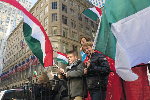 FILE- In this Oct. 10, 2016, file photo, boys wave Italian flags while riding a float in the Columbus Day Parade in New York. A movement to abolish Columbus Day and replace it with Indigenous Peoples' Day has new momentum but the gesture to recognize victims of European colonialism has also prompted howls of outrage from some Italian Americans, who say eliminating their festival of ethnic pride is culturally insensitive. (AP Photo/Mark Lennihan, File)