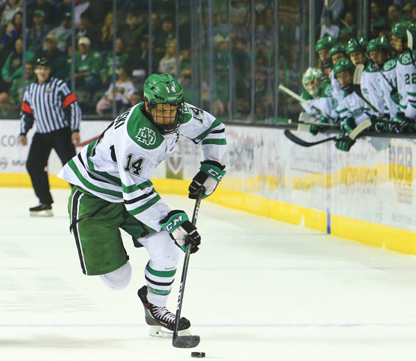 Senior forward and UND hockey captain Austin Poganski drives the puck past the blue line at the Ralph Engelstad Arena against Minnesota Duluth last season.