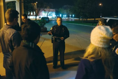 UND police chief Eric Plummer (center) assigns routes to groups during the fall campus safety tour outside Chester Fritz Auditorium on Thursday night.