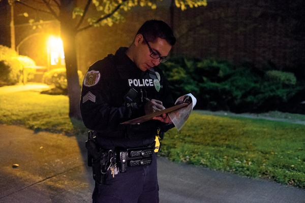 UND police sergeant Jose Solis notes a burned out light during the fall campus safety tour on Thursday night.