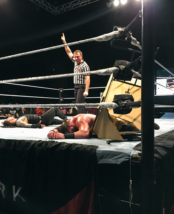 Roman Reigns (left) and Braun Strowman (right) lie on the mat after crashing through a table during the last man standing match Friday night at the Alerus Center.