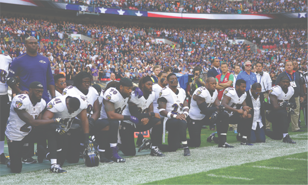 Players kneel on the Ravens sideline before the game in London versus the Jacksonville Jaguars. Joining the players was retired linebacker Ray Lewis, second from right.