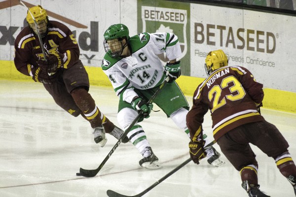 UND hockey captain Austin Poganski evades Minnesota's Ryan Lindgren (left) and Ryan Norman (right) during their matchup at the Ralph Engelstad Arena in October.