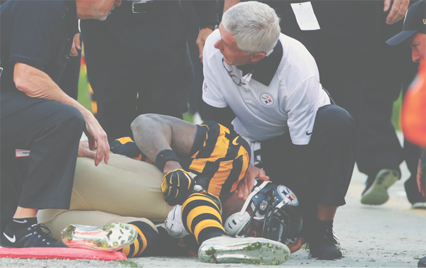 Pittsburgh Steelers running back LeVeon Bell (26) holds his knee as Steelers head trainer John Norwig tends to him after he was injured in the first half of an NFL football game against the Cincinnati Bengals, November 1, 2015 in Pittsburgh.
