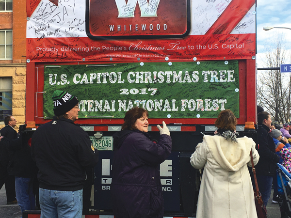 People sign a card accompanying the U.S. Capitol Christmas Tree during a stop in downtown Grand Forks on Sunday morning.