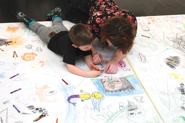 Liam Coons and his mother, Aimee, color on paper on the North Dakota Museum of Art gallery floor late Saturday morning.