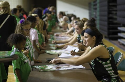 Fighting Hawks forward Fallyn Freije signs her autograph for a young fan during Fan Fest at the Betty Engelstad Sioux Center this past fall.