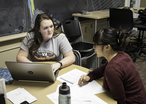 Ayla Rubenstein (right) assists Kaycie Ebert with a paper at the UND Writing Center in Merrifield Hall.