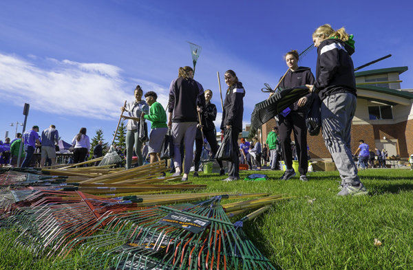 Members of the Fighting Hawks women's basketball team pick up rakes and other tools prior to volunteering for The Big Event last year.
